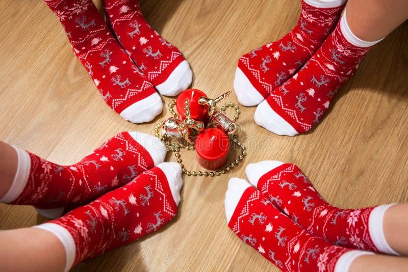 Quatre jambes de personnes portant les chaussettes rouges avec l'ornement de Noël placé autour des bougies sur le plancher photo libre de droits