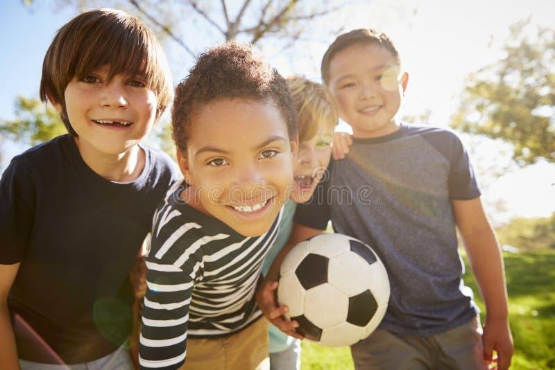 Quatre jeunes écoliers se penchant dedans à l'appareil-photo tenant le football photos libres de droits