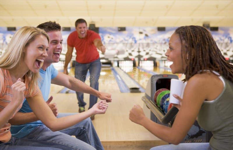 Quatre jeunes adultes encourageant dans une ruelle de bowling photographie stock libre de droits