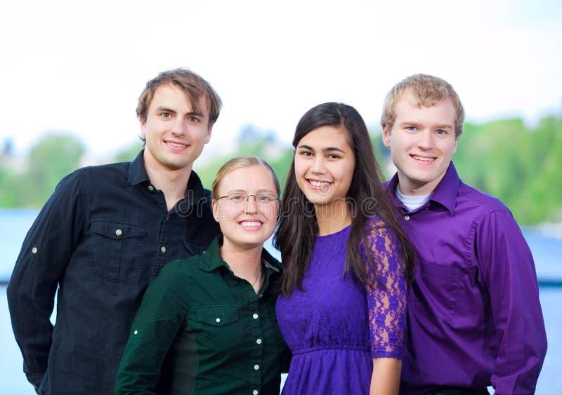 Quatre jeunes amis ethniques multi se tenant ensemble dehors image libre de droits