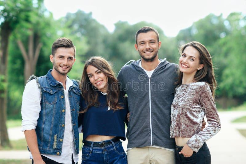 Quatre jeunes amis gais marchant le jour chaud images stock
