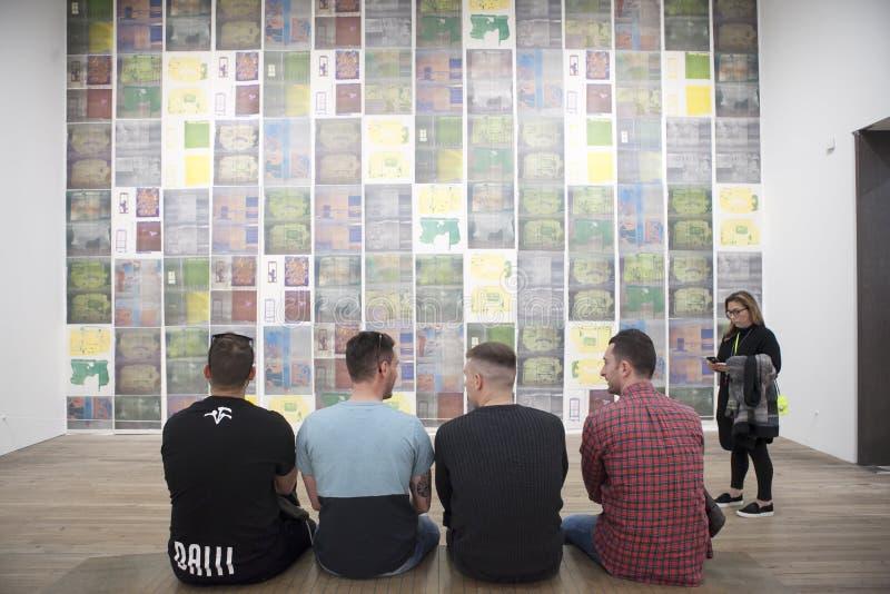 Quatre jeunes hommes s'asseyent sur un banc devant la peinture dans Tate Gallery photographie stock libre de droits