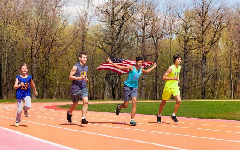 Quatre jeunes sprinters ondulant le drapeau américain sur la voie photo stock
