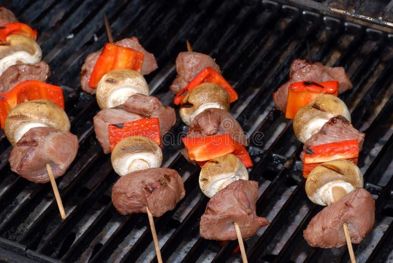 Quatre kabobs de boeuf sur un gril de barbecue images libres de droits