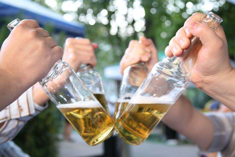 Quatre mains avec les bouteilles image libre de droits