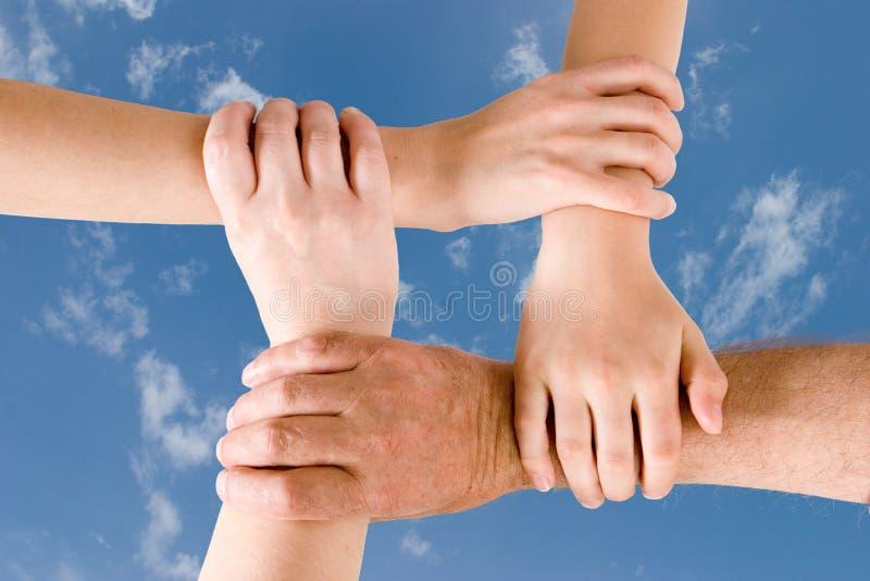 Quatre mains jointives ensemble photographie stock