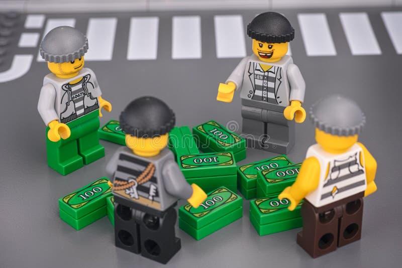 Quatre mini-personnages voleurs en Lego regardant une pile d'argent photos stock