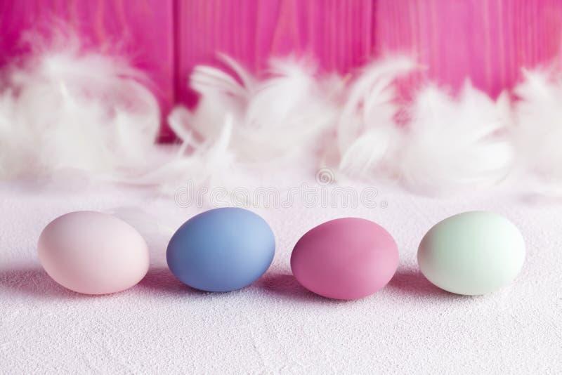 Quatre oeufs de pâques colorés et plumes blanches sur le fond en bois rose et table blanche image libre de droits