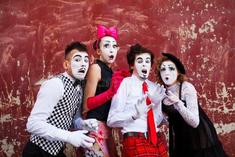 Quatre pantomimes dans le support de crainte à l'arrière-plan d'un mur rouge photo stock