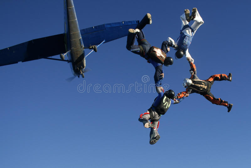 Quatre parachutistes sautent de l'avion photos stock