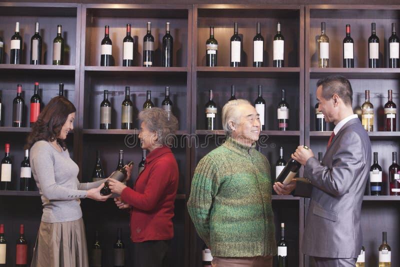 Quatre personnes examinant et discutant le vin à un magasin de vin photographie stock