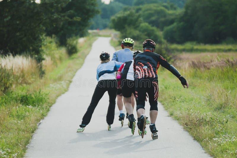 Quatre personnes plus âgées montant sur des patins de rouleau dans la ligne photo stock