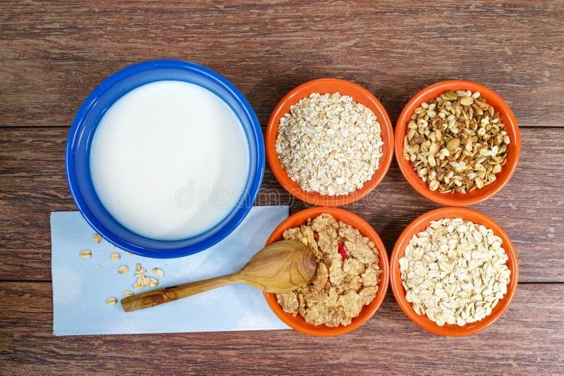 Quatre petites cuvettes avec différentes céréales et cuvette avec du lait, nourriture saine images stock