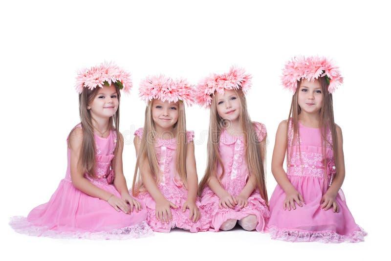 Quatre petites filles avec le long cheveu dans des robes roses photos stock