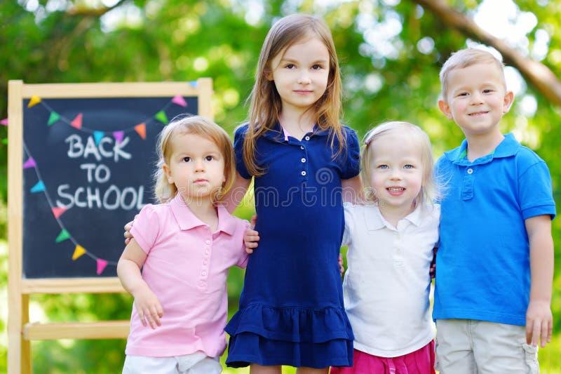 Quatre petits enfants adorables retournent à l'école photographie stock