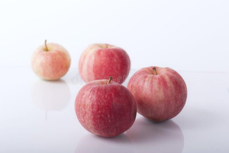Quatre pommes rouges mûres se trouvent sur un fond blanc photo stock