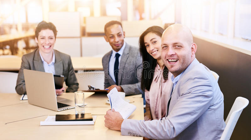 Quatre professionnels d'affaires regardant l'appareil-photo au cours d'une réunion images libres de droits