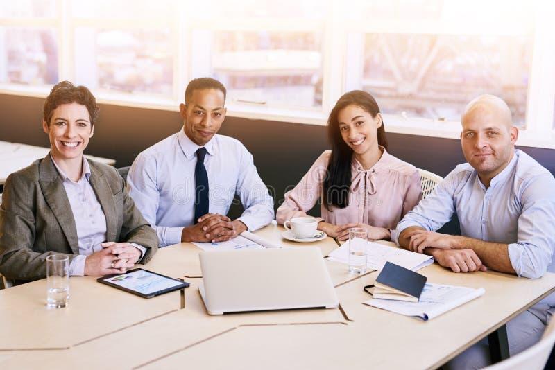 Quatre professionnels d'affaires regardant l'appareil-photo au cours d'une réunion image libre de droits