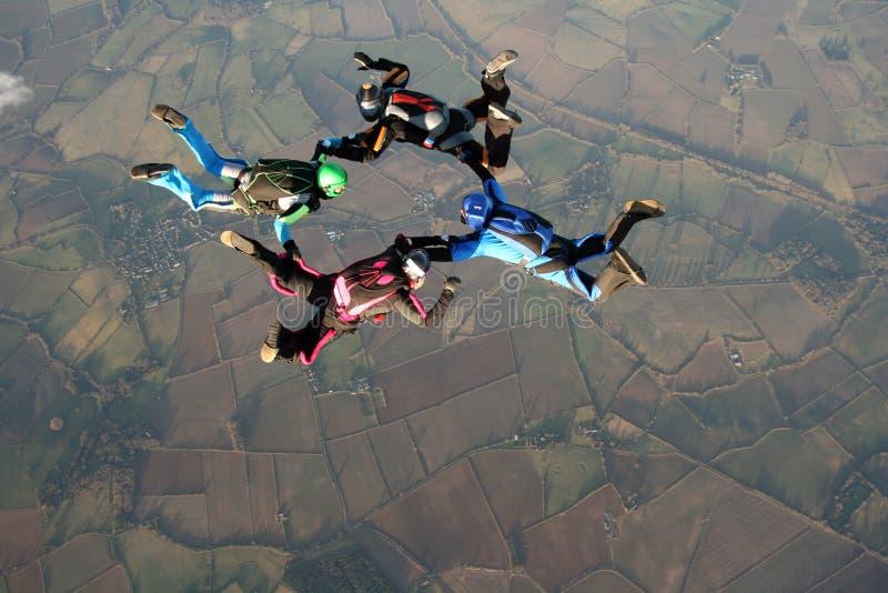 Quatre skydivers faisant des formations image stock