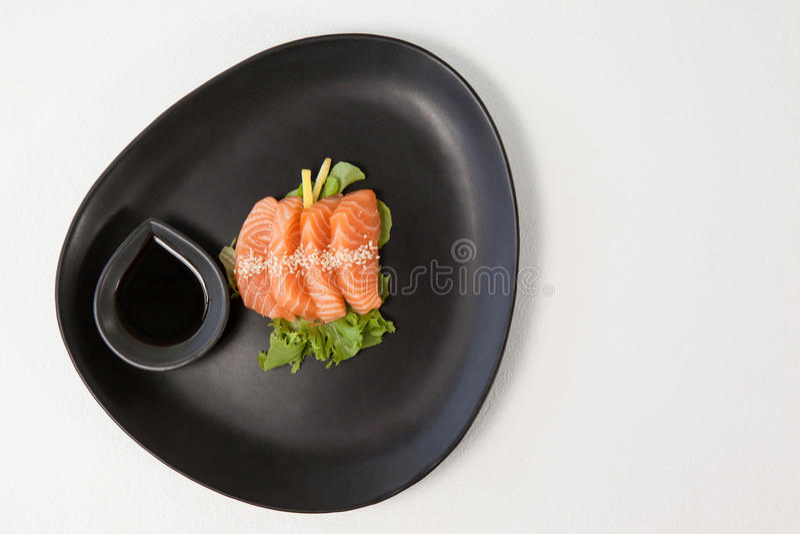 Quatre sushi de sashimi ont servi avec la sauce de soja dans le plat noir image libre de droits