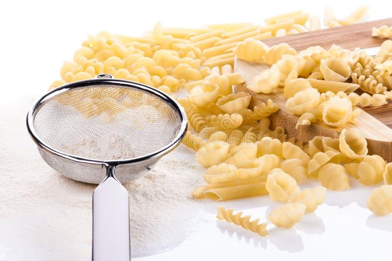 Quatre types de pâtes avec la fleur et l'ustensile de cuisine photographie stock libre de droits
