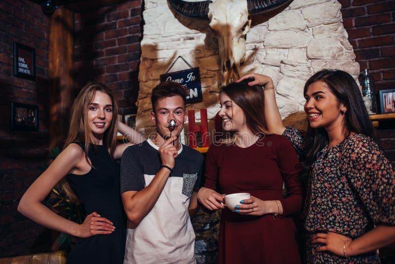 Quatro adolescentes frescos que vestem a roupa ocasional que levanta para a câmera em um à moda com design de interiores do aloja imagem de stock royalty free