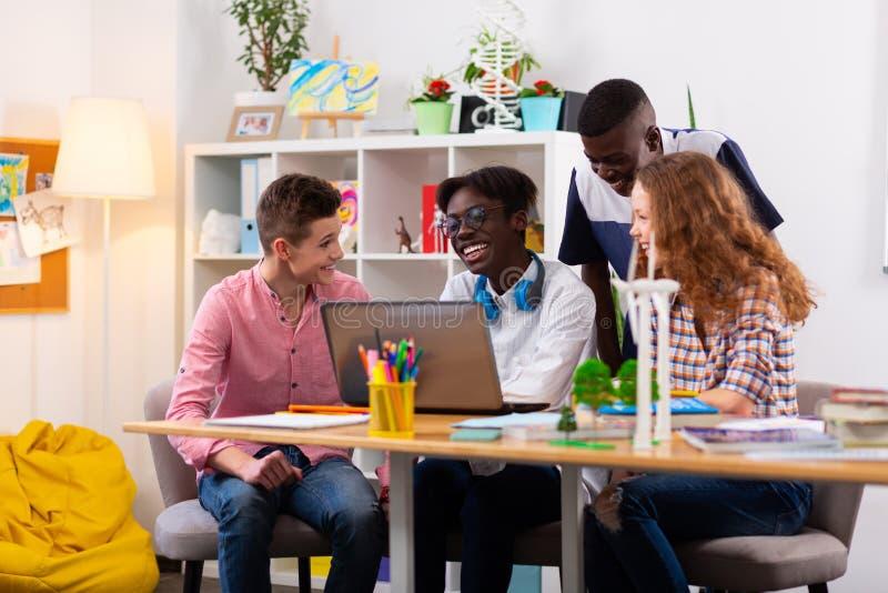 Quatro adolescentes que sentem alegres e positivos ao estudar junto imagem de stock royalty free