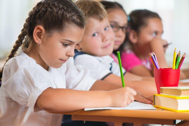 Quatro alunos diligentes que estudam na sala de aula fotos de stock royalty free