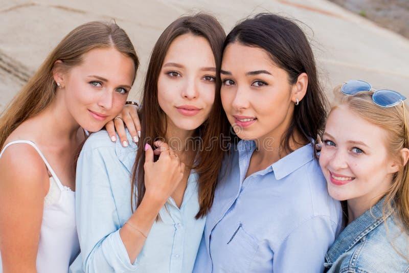 Quatro amigas que olham a câmera junto povos, estilo de vida, amizade, conceito do vocação imagem de stock