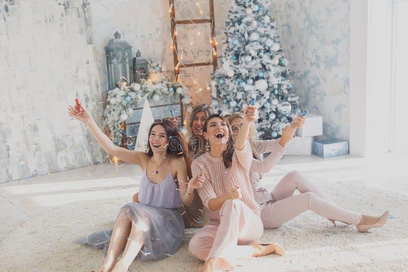 Quatro amigos bonitos alegres que comemoram o ano novo ou a festa de anos, têm o divertimento, álcool da bebida, dançando Caras e fotografia de stock royalty free