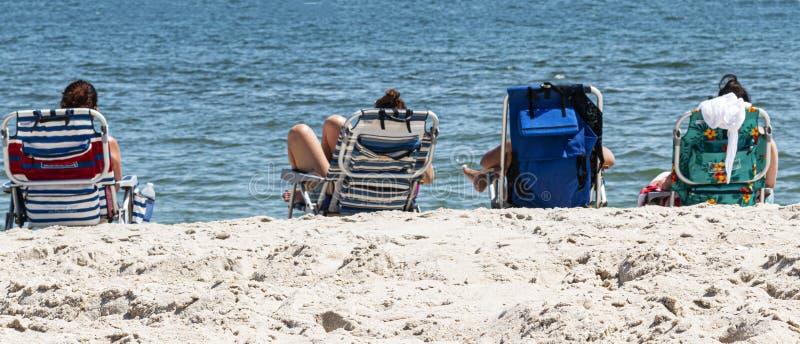 Quatro amigos em cadeiras de praia pelo oceano imagens de stock royalty free