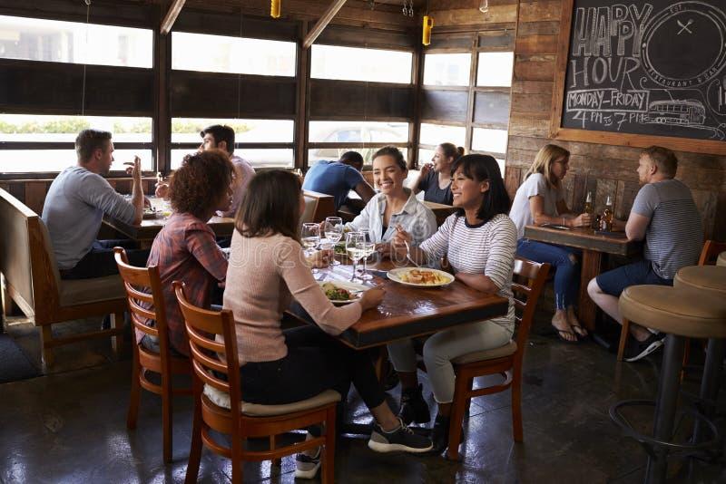 Quatro amigos fêmeas no almoço no restaurante ocupado, comprimento completo imagem de stock royalty free