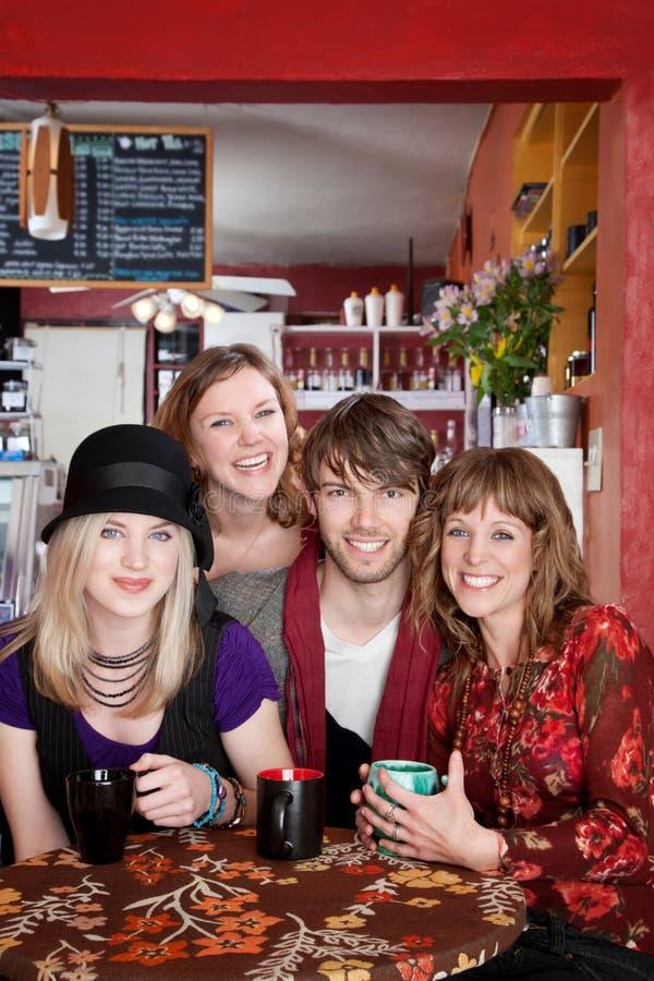 Quatro amigos felizes novos em um café fotos de stock royalty free