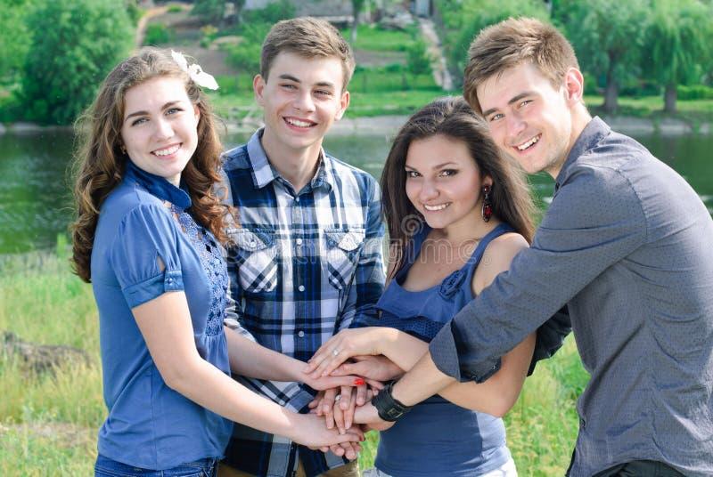Quatro amigos felizes que guardam as mãos gostam da equipe foto de stock royalty free