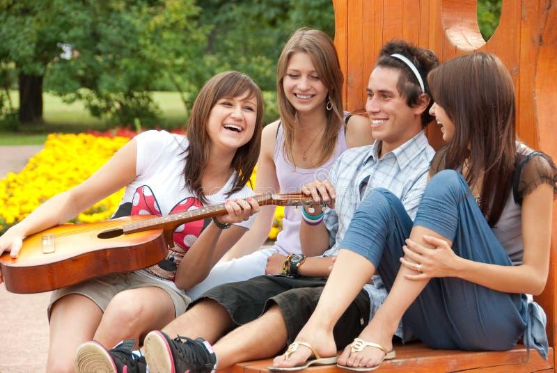 Quatro amigos novos jogam a guitarra fotografia de stock