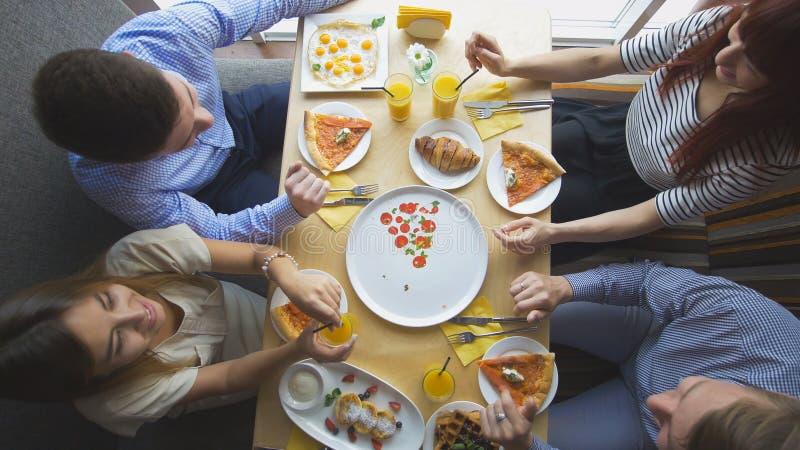 Quatro amigos novos que sentam-se no café e comem o café da manhã - pizza, suco, sobremesas imagem de stock royalty free