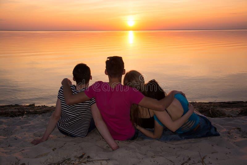 Quatro amigos que abraçam na praia e que admiram o por do sol imagens de stock