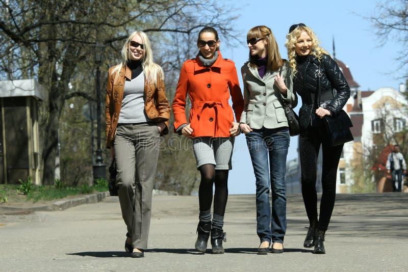Quatro amigos que andam na rua fotos de stock
