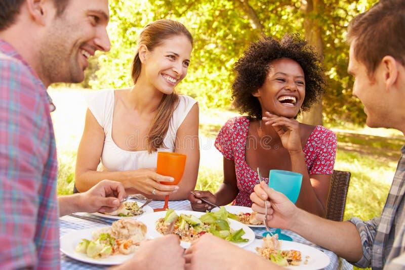 Quatro amigos que comem junto fora imagem de stock royalty free