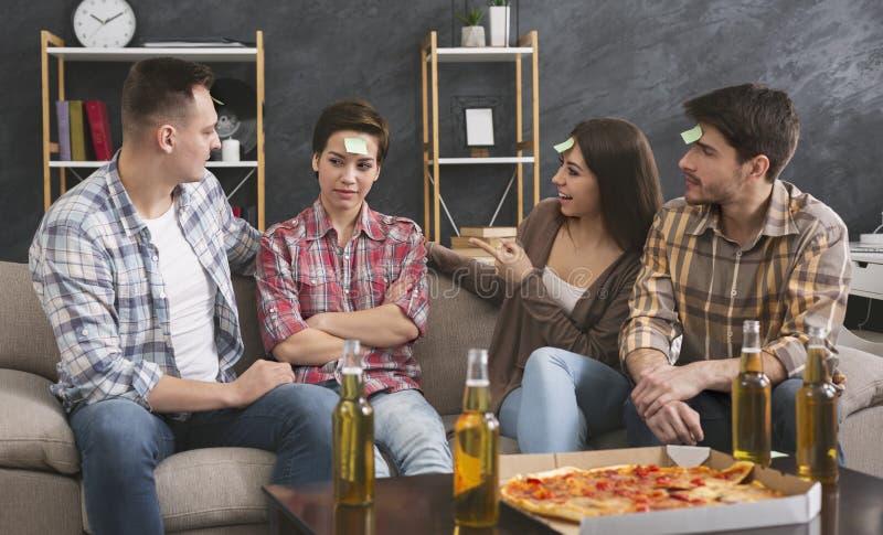 Quatro amigos que jogam a suposição do jogo que eu sou em casa fotografia de stock royalty free