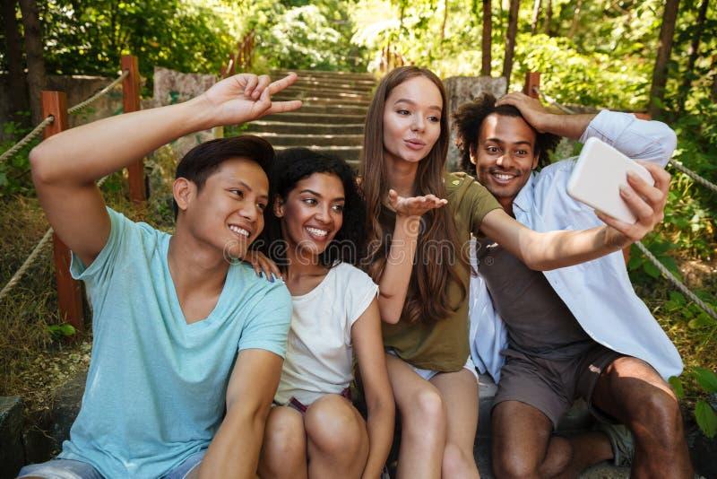 Quatro amigos que sentam-se em escadas na floresta imagens de stock royalty free
