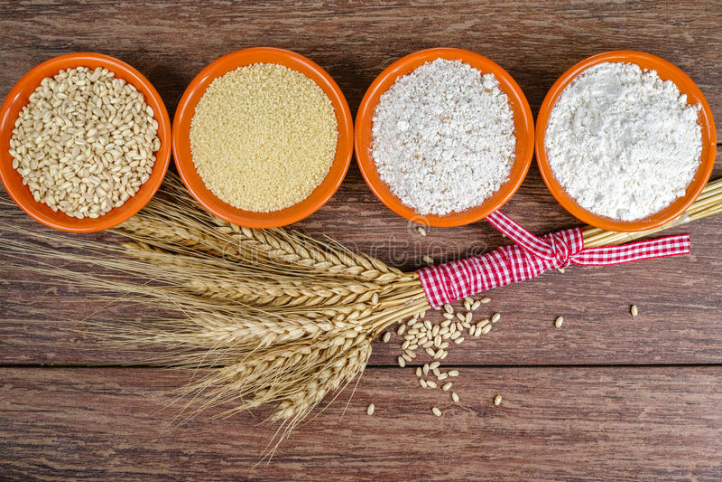 Quatro bacias pequenas com trigo, cuscuz, farinha de trigo inteiro, farinha de trigo e a polia inteiros das orelhas do trigo foto de stock