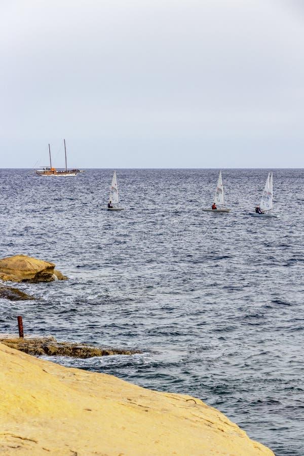 Quatro barcos de navigação e um navio de cruzeiros, vista do litoral da pedra calcária de Sliema, Malta foto de stock