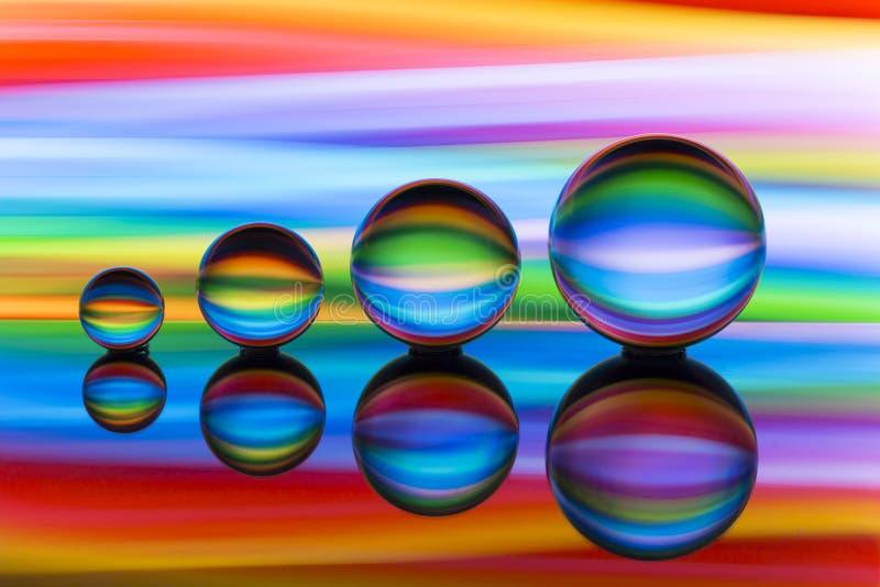 Quatro bolas de cristal em seguido com as raias coloridas da cor do arco-íris atrás delas fotografia de stock