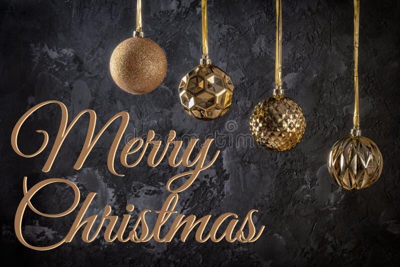 Quatro bolas douradas do Natal que penduram em fitas Ao lado do Feliz Natal da inscrição em um fundo textured preto imagens de stock