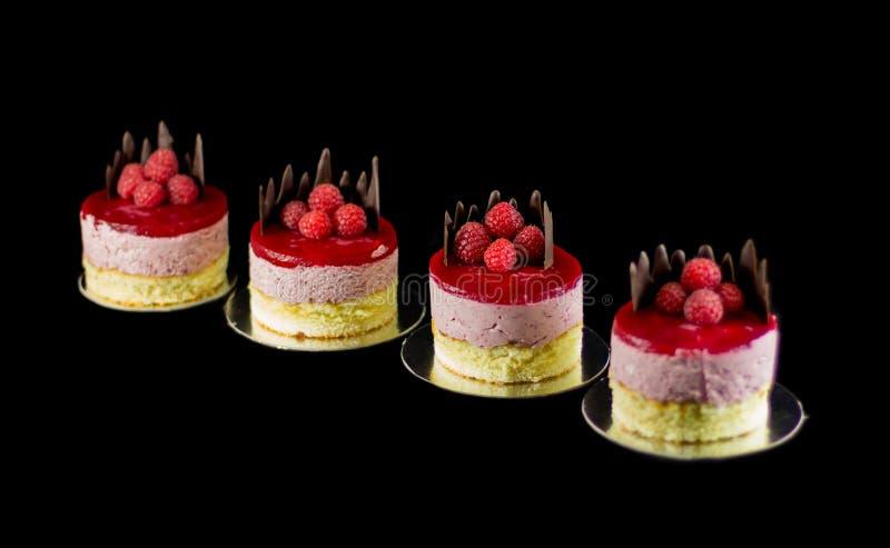 Quatro bolos pequenos com chocolate e framboesas fotografia de stock