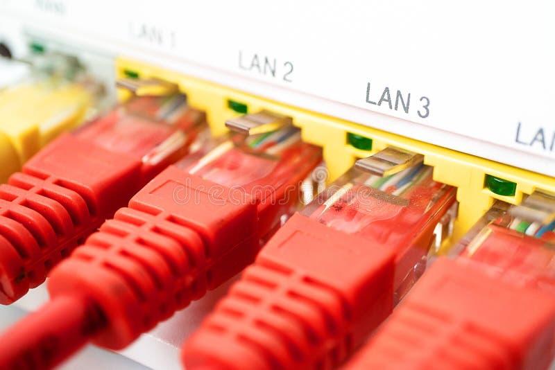 Quatro cabos de remendo vermelho são introduzidos em um roteador branco Conexão a internet imagens de stock