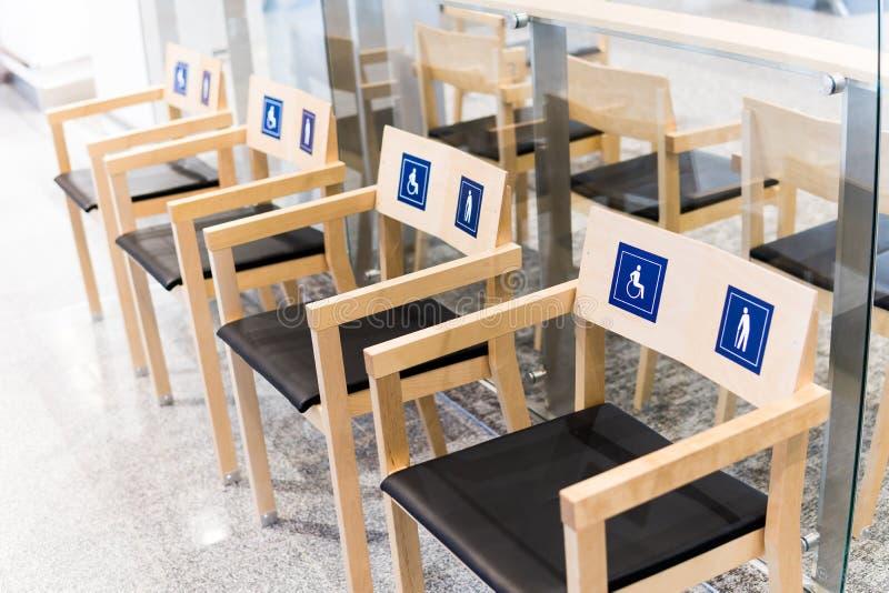 Quatro cadeiras de madeira no aeroporto com sinais para os enfermos e as pessoas idosas Atribuição de assentos públicos ao foto de stock royalty free