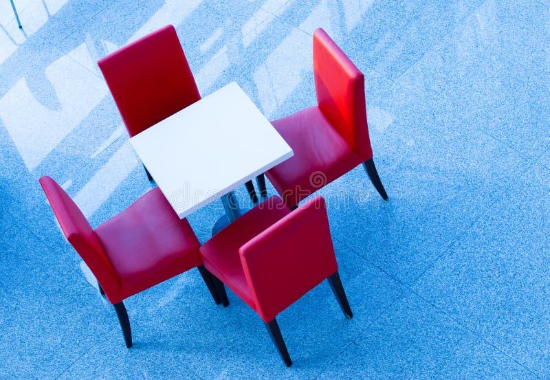 Quatro cadeiras vermelhas em uma tabela fotos de stock