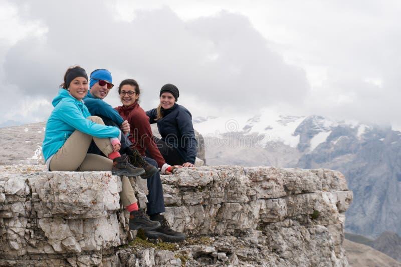Quatro caminhantes masculinos e fêmeas novos que sentam-se em uma borda do pico de montanha nas dolomites e que olham a vista sur imagem de stock